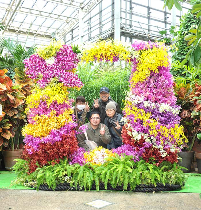 Visitors pose behind an orchid arrangement at International Orchid Show.